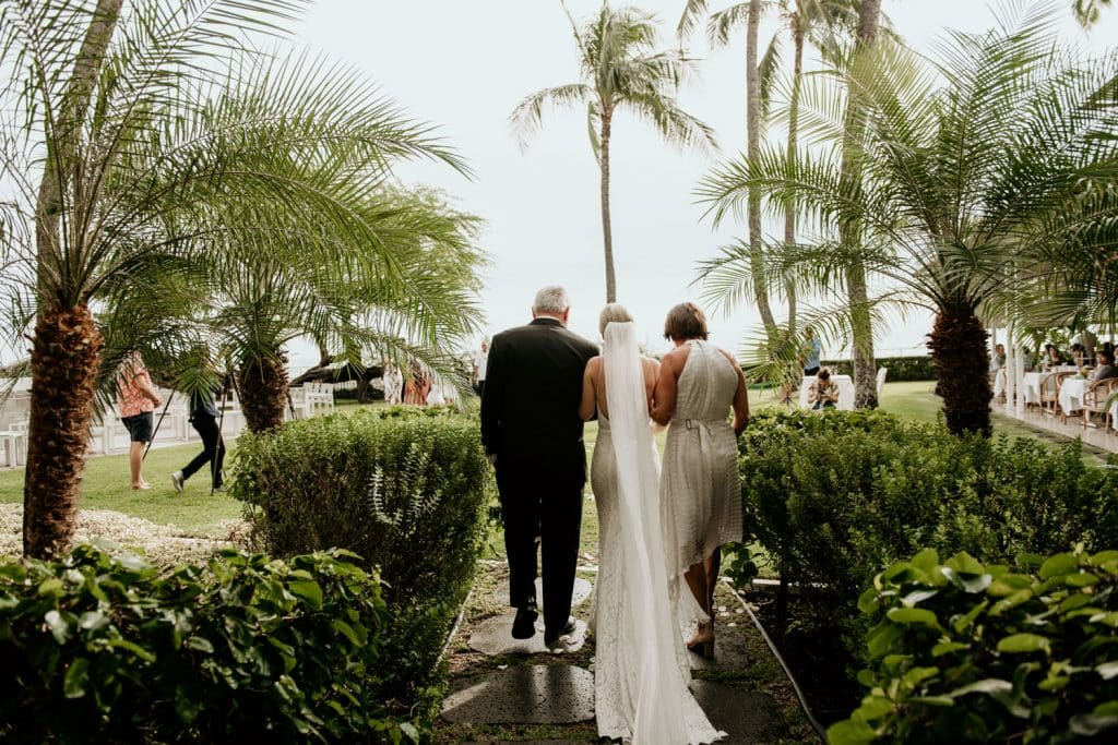 Back view of Bride walking down aisle with mother and father at Kawehewehe Lawn
