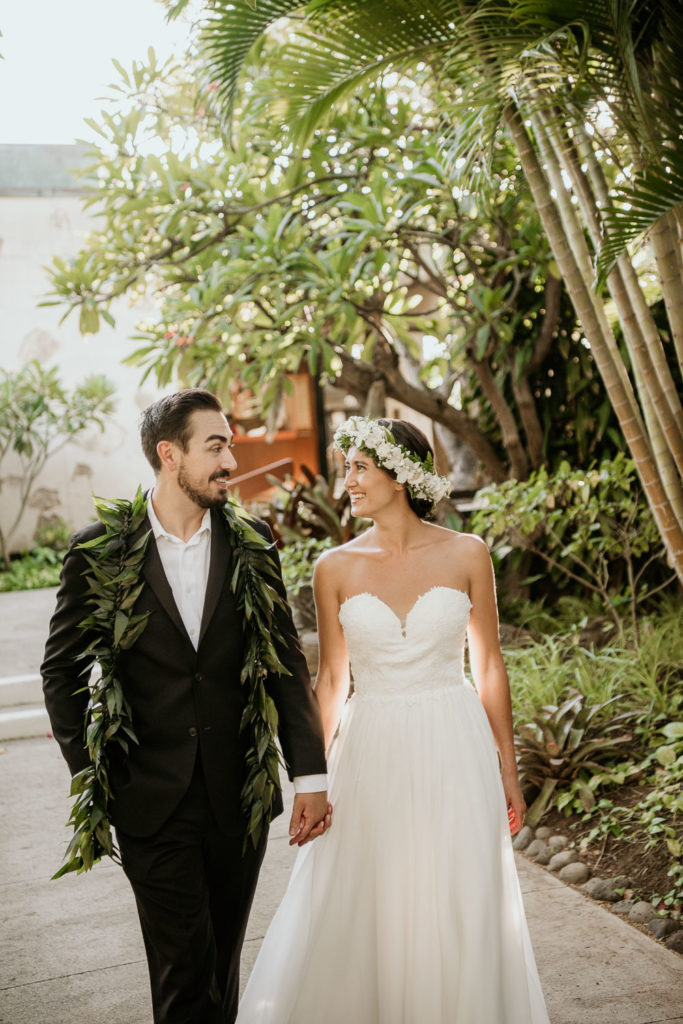 Bride and Groom walking at Outrigger Canoe Club Entrance